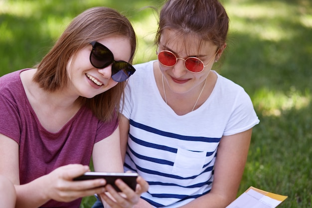 陽気な女性の若者のショットは、表情を喜ばせたり、携帯電話でコメディをオンラインで見たり、元気であったり、公園で屋外で自由な時間を過ごしたり、レクリエーションを楽しんだりしています。