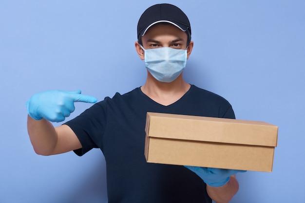 Макрофотография портрет доставщик в защитной маске и перчатках, парень держит посылку в руке и, указывая пальцем на коробку, доставляет заказы во время карантина