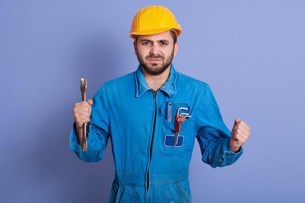 レンチを手に持って自信を持って労働者の半分の長さの肖像画は非常に怒っていて、怒りで拳を握りしめ、深刻な表情をしていて、制服とヘルメットを青で分離