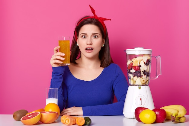 Закройте вверх женщины брюнет с стеклом свежего апельсинового сока в руке. дама любит здоровое питание, готовит коктейль дома удивленная женщина с блендером против розовой стены. диета и люди концепции.