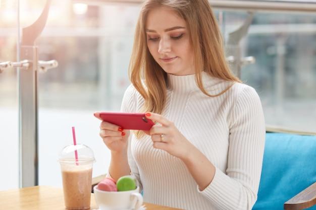 食堂のテーブルに座っている若い愛らしい女性の屋内撮影