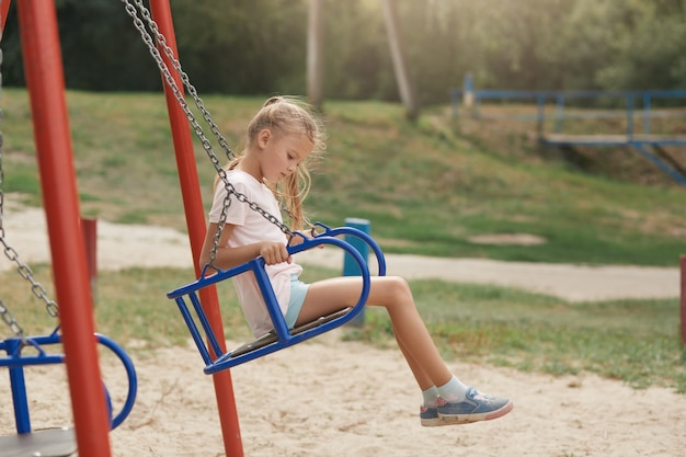Открытый выстрел очаровательная маленькая девочка на детской площадке с удовольствием в летнее время