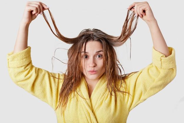 Красивая молодая женщина поднимает свои мокрые волосы, демонстрирует, что у нее есть некоторые проблемы, веселится в помещении, носит желтый халат, изолированный на белом