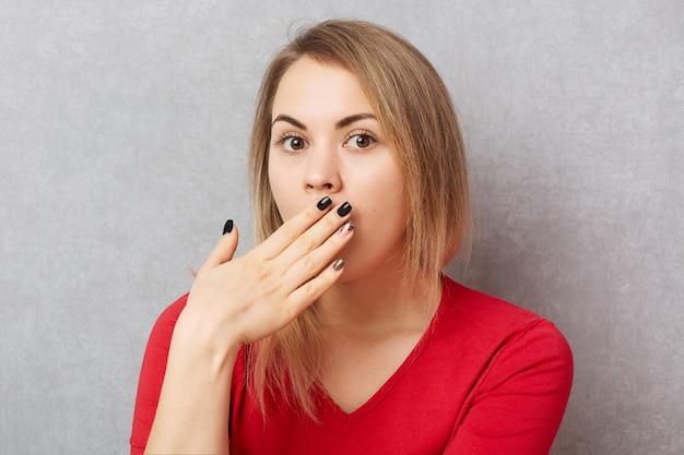 Удивленная женщина в шоке сплетничает со своей лучшей подругой, прикрывает рот руками, слышит неожиданные интригующие новости, изолированные на сером