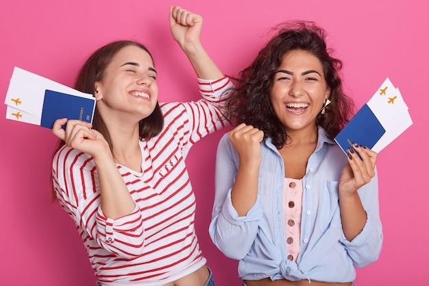 ばれ、休暇!チケットとパスポートをバラのスタジオに持っている女性、拳を握りしめている女性、幸せを表現している女性、夢が叶います。