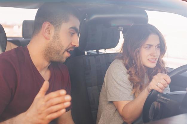困惑した若い女性ドライバー研修生が車を運転します。