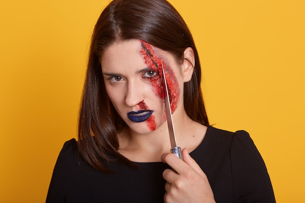 彼女の顔の近くにナイフを持って血を流している少女の室内撮影