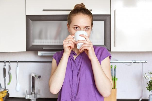 Снимок в помещении приятной на вид молодой милой женщины носит фиолетовую повседневную одежду