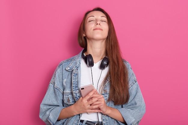 Молодая девушка в стильной джинсовой куртке, держит в руках мобильный телефон, держит голову закрытыми глазами, чувствует благодарность