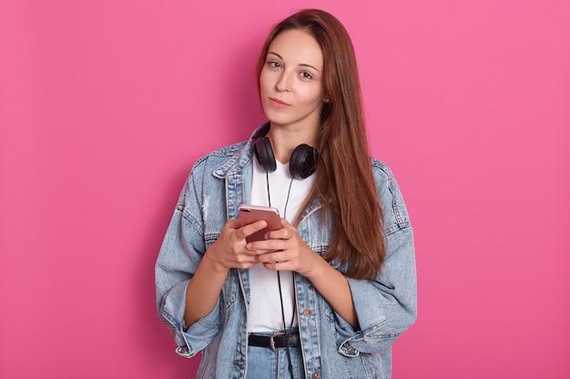 スマートフォンを両手で持ち、バラ越しにカメラを見ている魅力的な女性は、スタイリッシュな服を着ており、首にヘッドホンがあり、音楽を聴くのが好きで、深刻に見えます。