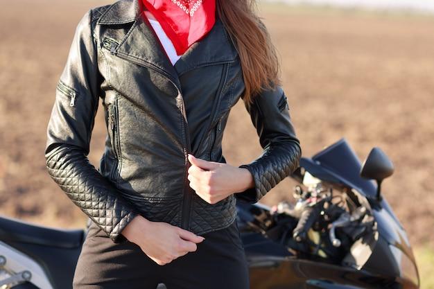 スポーティな女性のトリミングされた画像は、彼女の黒い革のジャケットをジップし、レース競技またはマラソンの準備をし、バイクの近くでポーズをとり、極端なスポーツを楽しんでいます。