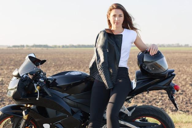 魅力的なモーターサイクリストの水平ショットは、バイクに傾いて、ヘルメットに手をかざし、バイクの近くに立ち、革のジャケットを身に着けており、屋外モデルです。人、高速、目的地のコンセプト