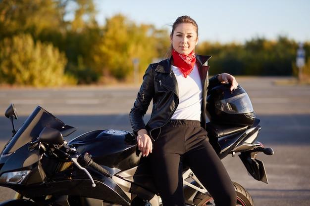 Красивая женщина-водитель сидит на черном мотоцикле, носит кожаную куртку, черные брюки, белую рубашку и красную бандану на шее, останавливается на дороге, чтобы отдохнуть