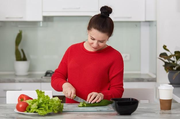 妊娠中の女性が自宅で料理、夕食に新鮮なグリーンサラダをやって、妊娠中に健康的な妊娠の概念、赤いカジュアルセーターを着ている女性に多くの異なる野菜を食べての屋内撮影。