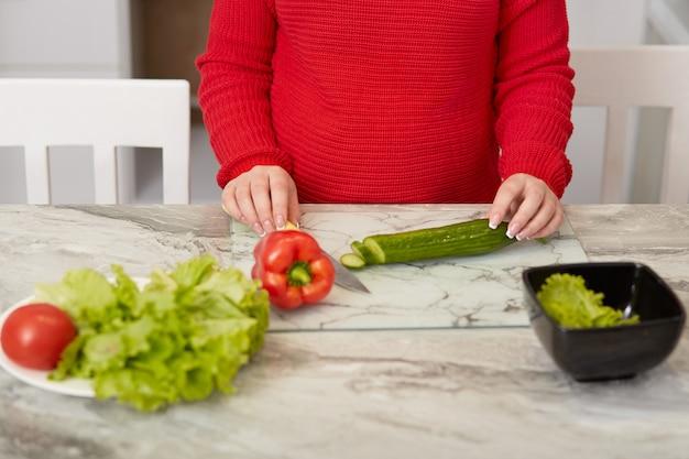 調理時間の概念。トリミングされた画像は、妊娠中の新鮮な野菜サラダを準備し、ナイフでキュウリ、コショウ、トマトをカットし、台所のテーブルでポーズをとり、赤い暖かいセーターを着ています。栄養の概念