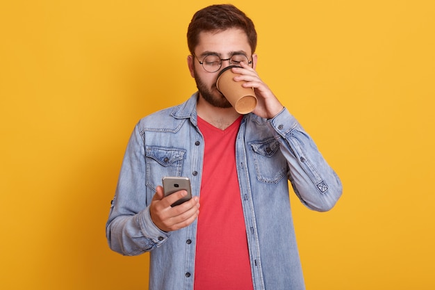 テイクアウトのコーヒーやお茶を飲んだり、スマートフォンを手に持ってその画面を見たり、赤いカジュアルシャツやデニムジャケットを着て魅力的な若い男。