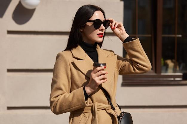 通りの建物の上に孤立した若い美しい屋外ファッション写真、エレガントな女性がサングラスを持ち上げて目をそらしながら、一人で歩きながらホットテイクアウトの飲み物を楽しんでいます。