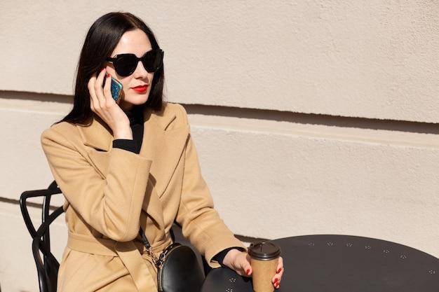Яркая очаровательная молодая самка разговаривает по телефону, разговаривает, звонит друзьям, пьет горячий кофе, сидит на светлой стене на улице, выглядит мирно. концепция свободного времени.