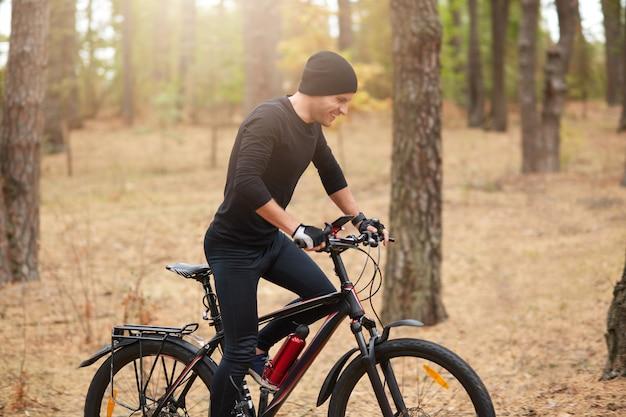 Молодой спортивный байкер, езда на велосипеде в вдохновляющие лесной пейзаж. человек ездит на велосипеде по тропе эндуро, преодолев назначенное расстояние, надев черную спортивную одежду и кепку, наслаждаясь активным отдыхом.
