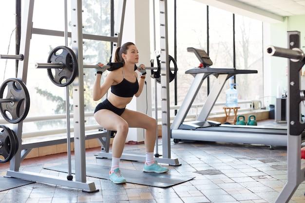 ジムで運動をしているプロのスポーツウーマン、バーベルでスクワット、ウェイトを持ち上げ、筋肉の強さと定義を発達させ、ファッションスポーツユニフォームを着て、ポニーテールを持ち、健康を保ちます。