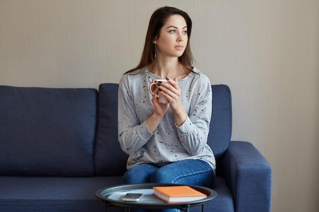 カジュアルなジャンパーとジーンズに身を包んだ、思いやりのあるきれいな女性は脇に焦点を当て、ホットドリンクのマグカップを保持している、モダンなアパートメントのソファーに座っている、スマートフォンとメモ帳付きのコーヒーテーブル、深く考える