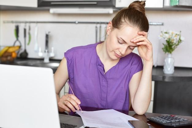 Молодая домохозяйка подсчитывает семейные расходы, оплачивает счета за аренду и бензин, просматривает документы, работает с ноутбуком, садится за кухонный интерьер, одетая в повседневную фиолетовую футболку.