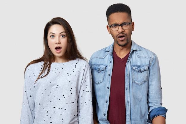 Студийный снимок удивленной испуганной пары разных народов смотрит на камеру, глаза полны страха, стоят на белой стене студии, поражены выражением лица, видят что-то ужасное.