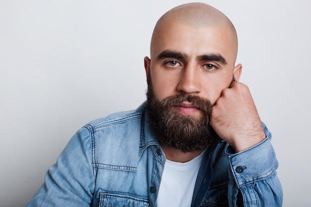 Горизонтальный крупный план красивого лысого мужчины с очаровательными темными глазами, густыми черными бровями и бородой в джинсовой рубашке, держащей руку на подбородке, думая о чем-то.