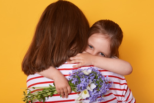 美しい若い女性と彼女の魅力的な小さな娘が屋内を抱き締めます。子供は母の日でお母さんを祝福し、花を贈り、ミイラはストライプのシャツを着て後ろ向きに立ちます。