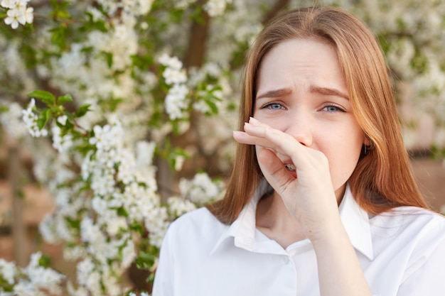 Открытый снимок грустного подчеркнутого красивого молодого самка потирает нос, поскольку имеет аллергию на цветение, носит изящную белую рубашку, позирует против цветущего дерева