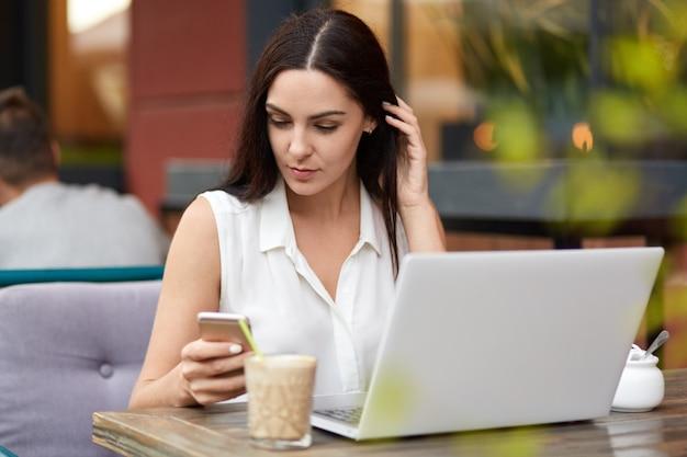 Занятая молодая женщина-фрилансер с темными волосами работает на ноутбуке, получает сообщение на смартфон, набирает обратную связь, пьет кофе или капучино в кафетерии на открытом воздухе, имеет серьезное выражение.