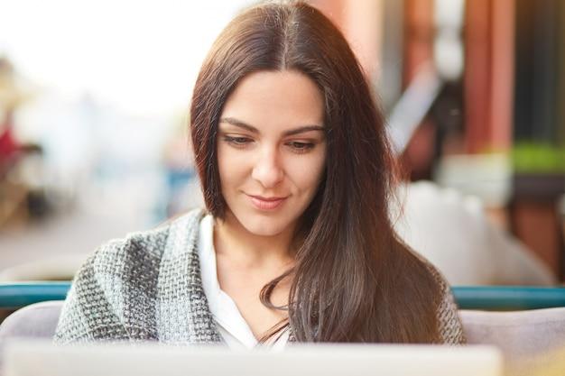 ラップトップコンピューターに焦点を当てた美しいブルネットの女性は、表現を満足させ、屋外のコーヒーショップでポーズをとり、最新のラップトップデバイスでオンラインでチャットし、リモートで作業し、インターネットのウェブサイトをオンラインで開発しています