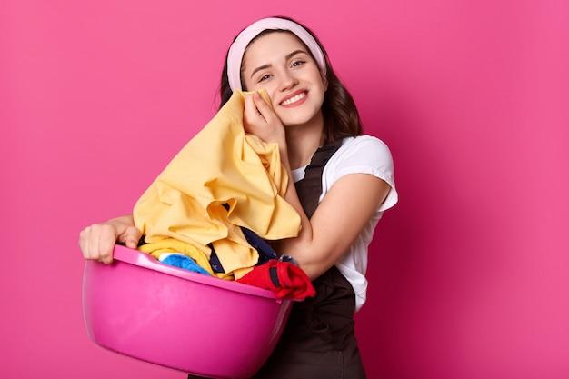 Съемка в помещении веселой привлекательной домохозяйки в белой повязке на голову