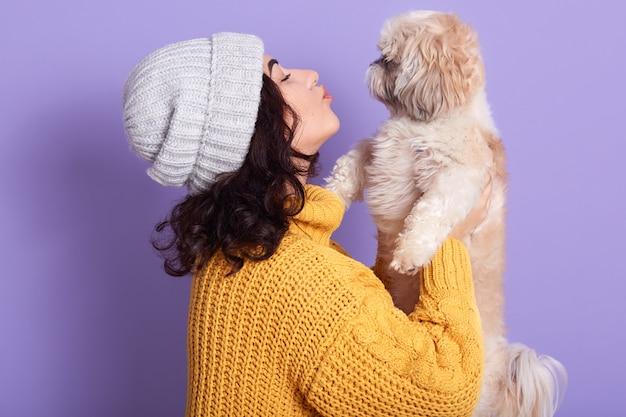 ライラックの上に孤立して立っている魅力的なうれしそうな若い女の子の水平スタジオショット、彼女のマルチーズ犬を手で押し、キス、ペットをとても愛しています。