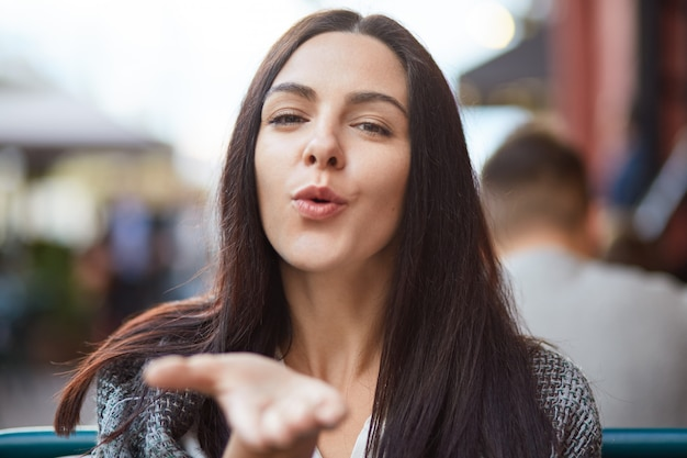 魅力的な愛情深い女性がカメラにエアキスを吹く、長い黒髪、距離にさよならを言う、屋外でポーズ、恋人といちゃつく