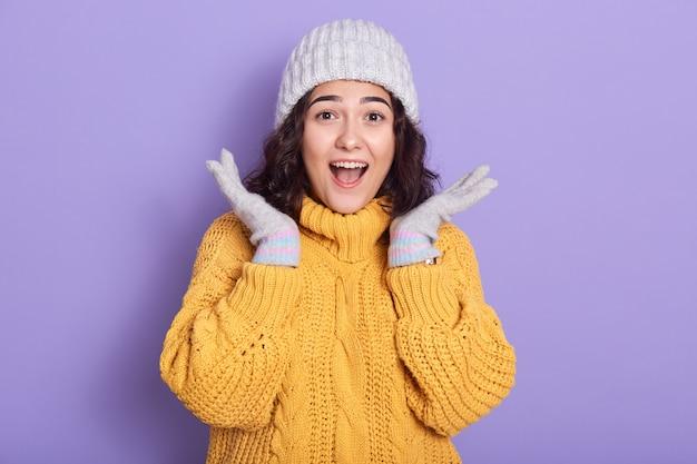 ショックを受けて感銘を受けた美しい若い女性が手を上げ、口と目を大きく開いて、黄色いセーターと白い帽子、手袋、ライラックの上に立って立っている身に着けているの画像