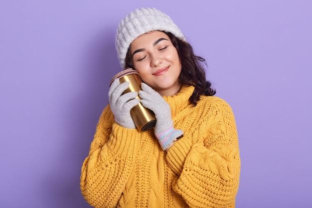 Горизонтальный внутренний снимок нежной мирной молодой брюнетки, закрывающей глаза, улыбающейся, держащей термокружку, надевающей ее близко к лицу, в белой шляпе, перчатках и ярко-желтом свитере.