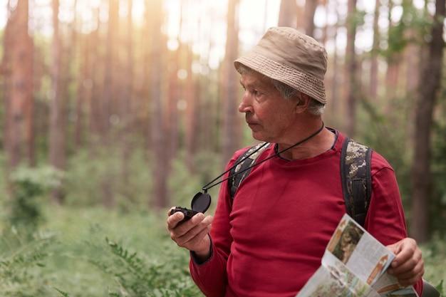 赤いカジュアルセーターと帽子をかぶったハイカー。バックパックでポーズをとり、コンパスで正しい方向を探し、森に迷い込み、輝く黄金の太陽に照らされた。