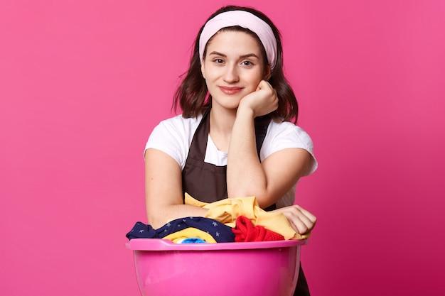 Изображение женщины стоит возле огромного розового бассейна со свежей одеждой