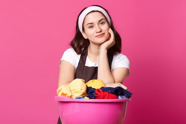 Милая молодая домохозяйка с розовым тазом, полным чистых помытых вещей