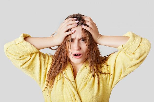 Разочарованная женщина касается головы, имеет влажные волосы и расстройство