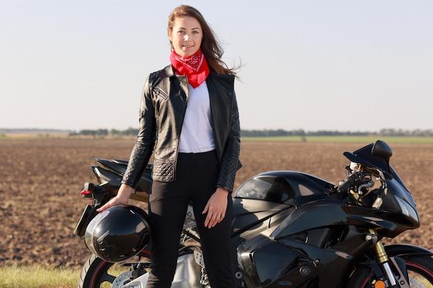 Открытый выстрел привлекательная женщина водитель с темными волосами стоит возле черного быстрого мотоцикла