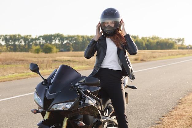 Горизонтальный вид стильной уверенной женщины байкер, одетый в модную одежду