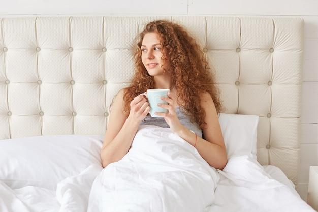 巻き毛を持つかなり若い女性がベッドで朝の芳香族コーヒー