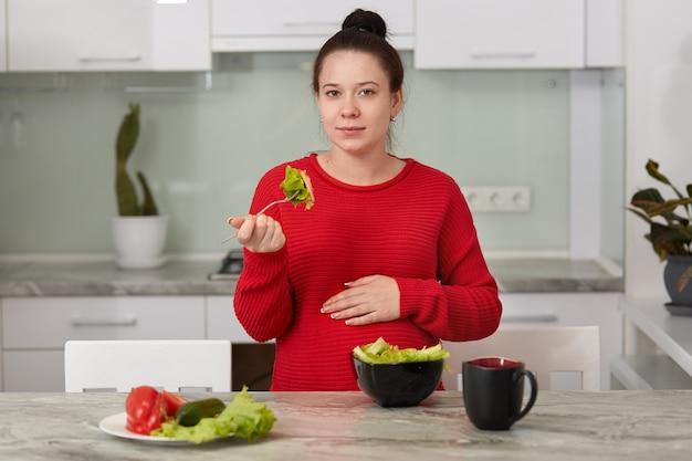 自宅のキッチンで若い妊婦