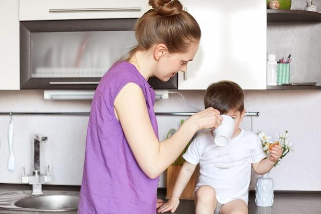 Портрет молодой мамы напивает ее маленького сына, который сидит на кухонной мебели