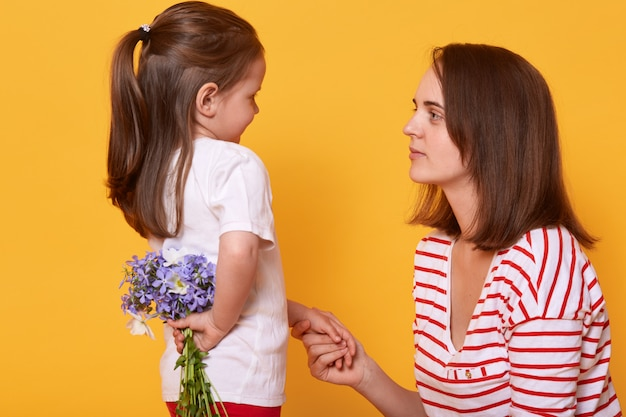 С днем матери! милая девочка ребенка поздравляет маму с праздником и хочет дарить цветы.