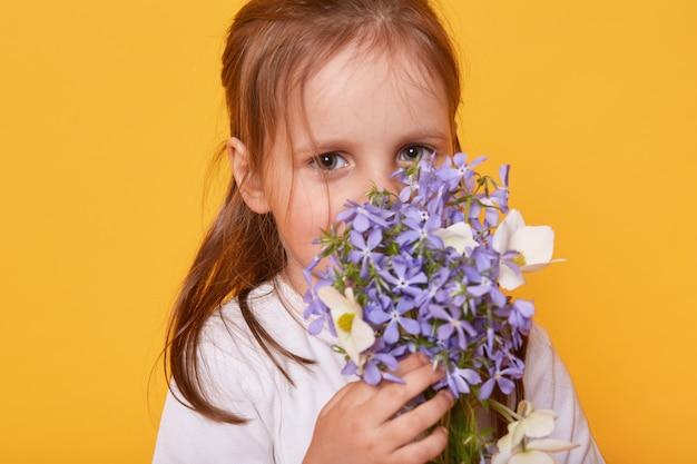 Студия выстрел милая маленькая девочка в белой рубашке пахнущий букет цветов