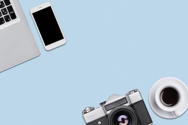 Ретро камера, современный портативный компьютер, смартфон и чашка кофе, лежа на синем фоне плоской. современные и ретро материалы на плоской поверхности. вид сверху рабочего места фотографа с копией пространства