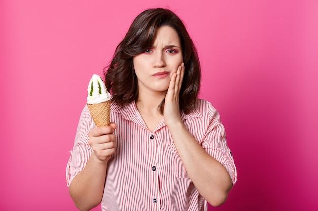 魅力的な女性で、新鮮なミルクアイスクリームを保持し、頬に手をかざし、歯痛があります。敏感な歯の病気からブルネットサーファー、冷たいサンデーを食べ、ピンクの壁の上に立つ